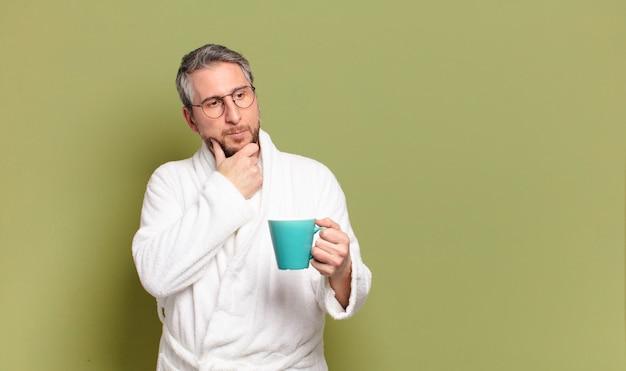 Мужчина среднего возраста просыпается с чашкой кофе