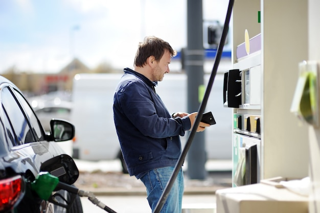 Middle age man filling gasoline fuel in car