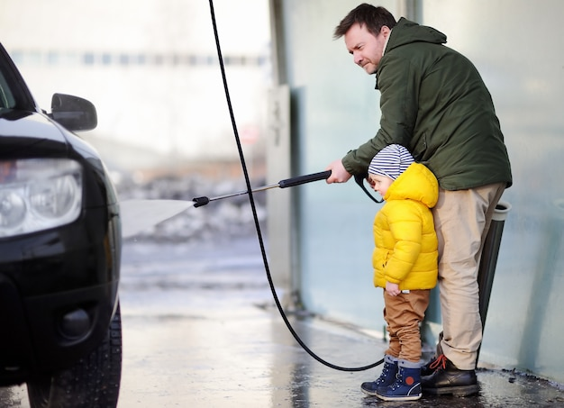 Middle age man and his little son washing a car on a carwash. family time