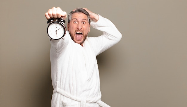 Middle age man holding a clock surprised