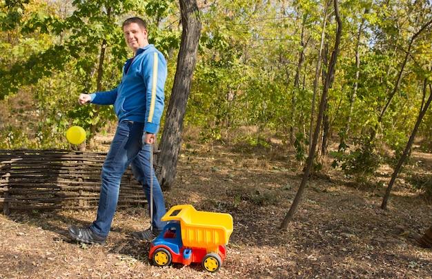カメラを見ながら森で色付きのトラックのおもちゃを遊んでいる秋の服の中年男性。