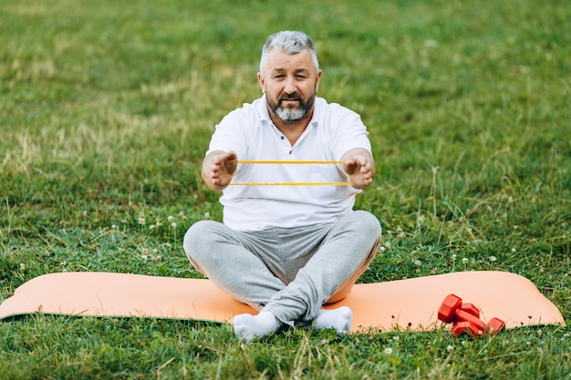 Middle age  man  taking exercise with tape outdoor.  sport