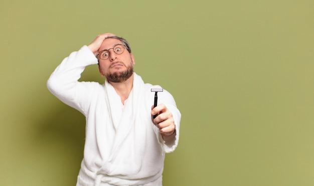 バスローブとかみそりを身に着けている中年男性