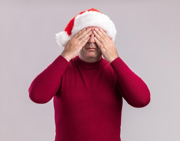 白い壁の上に立っている手で目を覆うクリスマスサンタの帽子をかぶっている中年男性