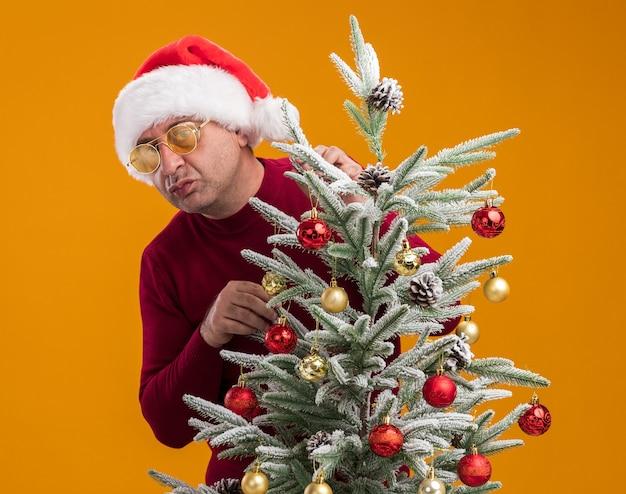 Uomo di mezza età che indossa il cappello della santa di natale in dolcevita rosso scuro e occhiali gialli che decorano l'albero di natale che guarda l'obbiettivo confuso e dispiaciuto in piedi su sfondo arancione