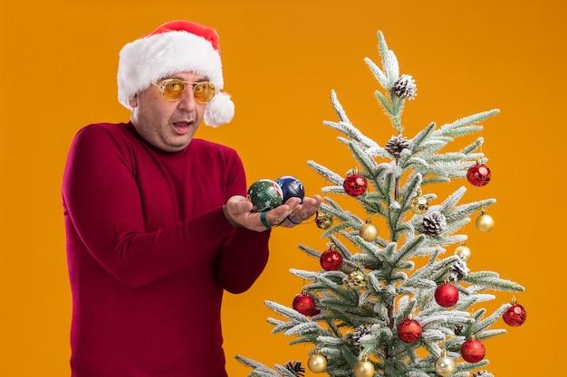 Uomo di mezza età che indossa il cappello di babbo natale in dolcevita rosso scuro e occhiali gialli tenendo le palle di natale guardando sorpreso in piedi accanto a un albero di natale su sfondo arancione