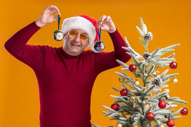 Uomo di mezza età che indossa il cappello di babbo natale in dolcevita rosso scuro e occhiali gialli tenendo le palle di natale sorridendo allegramente in piedi accanto a un albero di natale su sfondo arancione