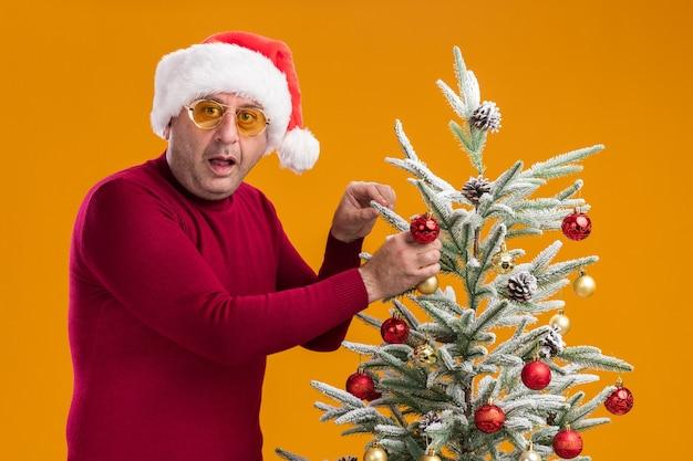 Uomo di mezza età che indossa il cappello di babbo natale in dolcevita rosso scuro e occhiali gialli che sembra sorpreso mentre decora l'albero di natale in piedi sul muro arancione