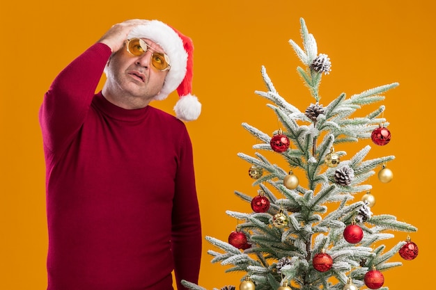 Middle age man wearing christmas santa hat in dark red turtleneck and yellow glasses looking up puzzled standing next to a  christmas tree over orange wall