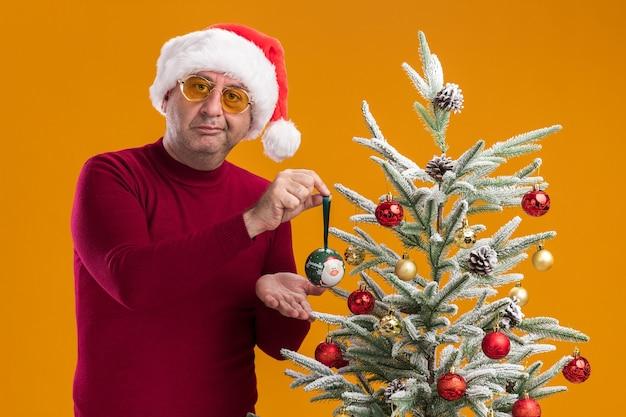 Uomo di mezza età che indossa il cappello di babbo natale in dolcevita rosso scuro e occhiali gialli con un sorriso scettico che decora l'albero di natale