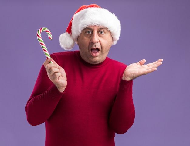 Мужчина среднего возраста в рождественской шляпе санта-клауса с конфетой в руках, счастлив и удивлен, подняв руку, стоя над фиолетовой стеной