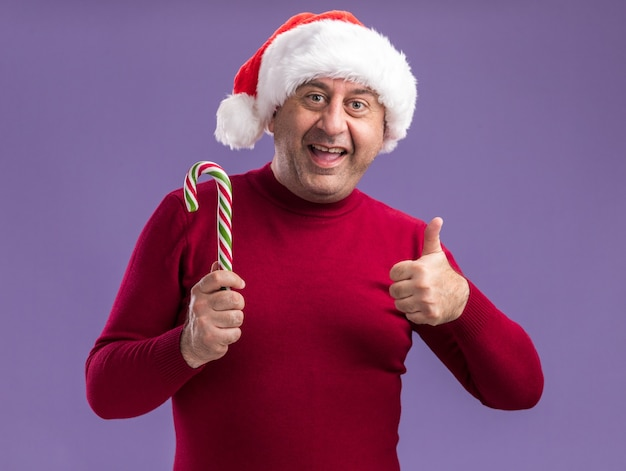 Middle age man wearing christmas santa hat holding candy cane  with smile on face showing thumbs up standing over purple wall