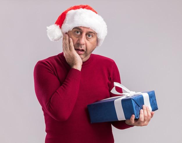 크리스마스 선물을 들고 크리스마스 산타 모자를 쓰고 중년 남자가 놀란 흰 벽 위에 서 놀란