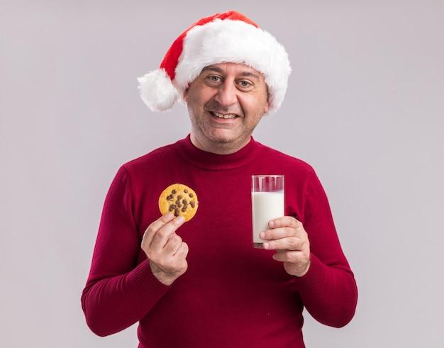 Uomo di mezza età che indossa il cappello di babbo natale con in mano un bicchiere di latte e un biscotto sorridendo felice e allegro in piedi su un muro bianco
