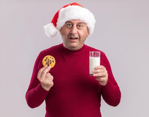 白い壁の上に立って幸せで陽気な笑顔のミルクとクッキーのガラスを保持しているクリスマスサンタの帽子をかぶった中年男性