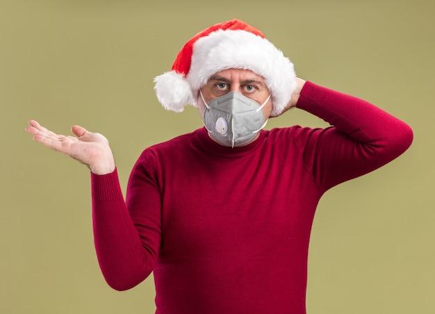 Мужчина среднего возраста в рождественской шапке санта-клауса в защитной маске смотрит в камеру, смущенный поднятой рукой, стоя на зеленом фоне