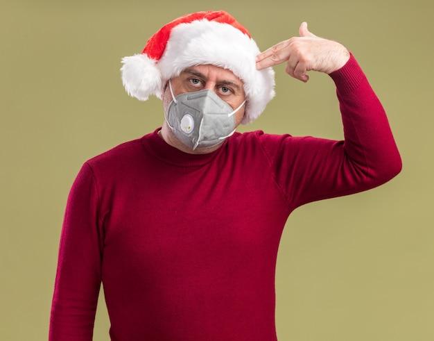 Uomo di mezza età che indossa il cappello di babbo natale che indossa la maschera protettiva per il viso guardando la telecamera stanco e annoiato facendo il gesto della pistola sopra la testa in piedi su sfondo verde