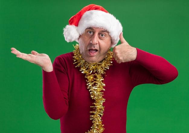 목 주위에 반짝이와 크리스마스 산타 모자를 쓰고 중년 남자가 엄지 손가락을 보여주는 혼란스러워 녹색 벽 위에 서있는 그의 손의 팔로 복사 공간을 제시
