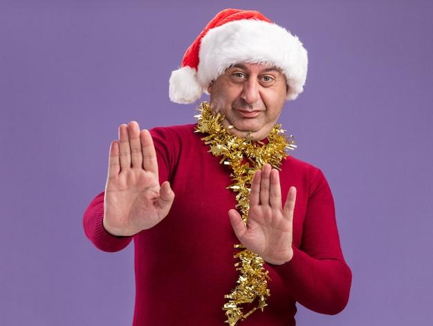 首に見掛け倒しのクリスマスサンタの帽子をかぶっている中年の男性は、紫色の壁の上に立って停止ジェスチャーを作る手を差し出すことに不満を持っています