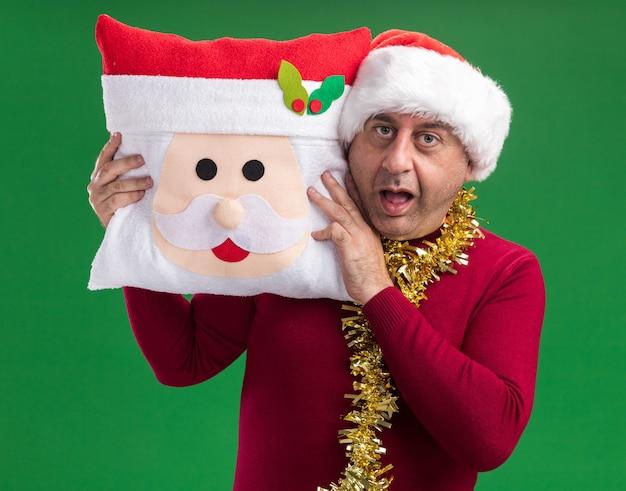 카메라를보고 크리스마스 베개를 들고 목 주위에 반짝이와 크리스마스 산타 모자를 쓰고 중년 남자는 놀랍고 녹색 배경 위에 서 놀란