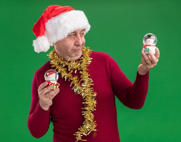 首の周りに見掛け倒しのクリスマスサンタの帽子をかぶっている中年の男は、選択をしようとして混乱しているように見えるクリスマスのスノードームを保持しています