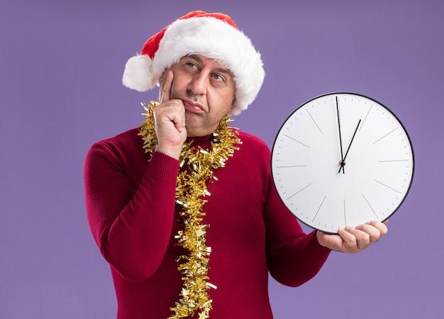 紫色の背景の上に立って困惑して脇を見て時計を保持している首の周りに見掛け倒しでクリスマスサンタの帽子をかぶっている中年の男
