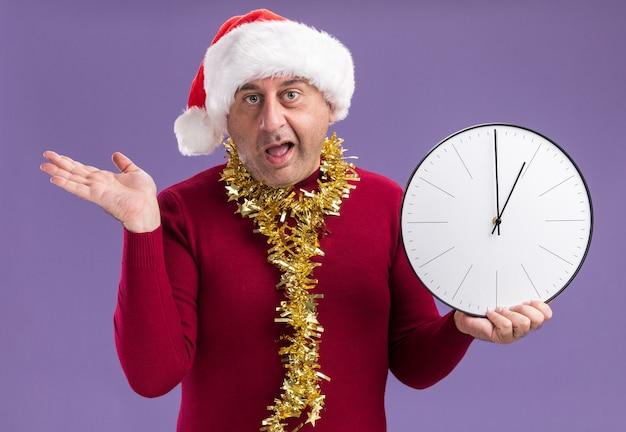 紫色の背景の上に立って腕を上げて混乱しているカメラを見て時計を保持している首の周りに見掛け倒しのクリスマスサンタ帽子をかぶっている中年男性