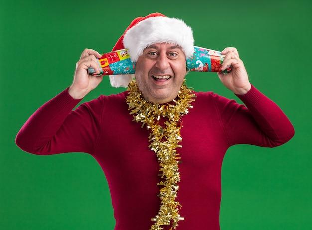 Uomo di mezza età che indossa il cappello di babbo natale con orpelli intorno al collo che tiene bicchieri di carta colorati sopra l'orecchio felice ed eccitato in piedi sul muro verde