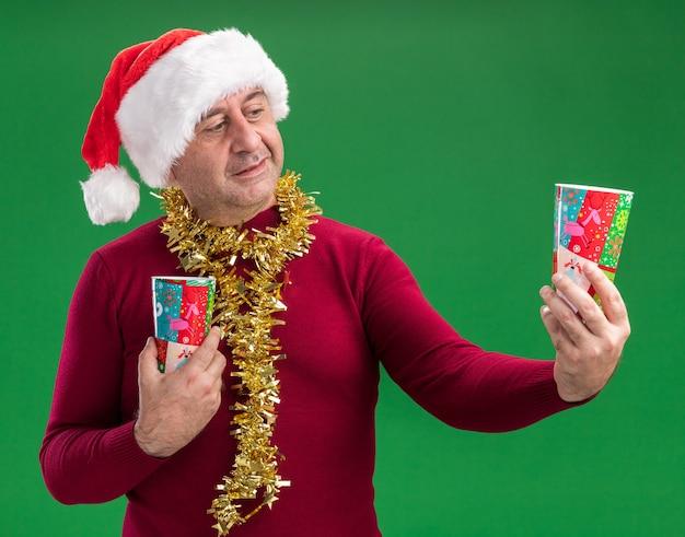 녹색 배경 위에 서있는 의심을 갖는 혼란 찾고 다채로운 종이 컵을 들고 목에 반짝이와 크리스마스 산타 모자를 쓰고 중년 남자