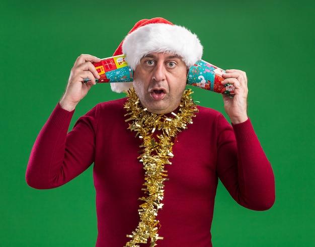 화려한 종이 컵을 들고 목에 반짝이와 크리스마스 산타 모자를 쓰고 중년 남자