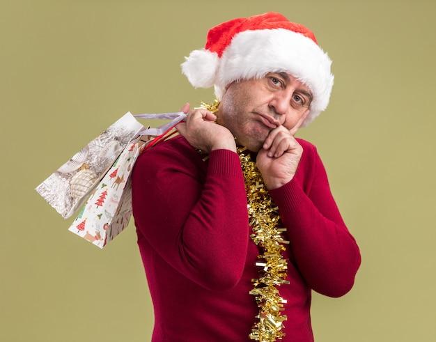 Uomo di mezza età che indossa il cappello della santa di natale con orpello intorno al collo che tiene i sacchetti di carta con i regali di natale che guarda l'obbiettivo stanco e annoiato in piedi sopra fondo verde