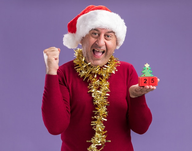 Мужчина средних лет в рождественской шляпе санта-клауса с мишурой на шее держит игрушечные кубики с датой двадцать пять счастливых и возбужденных, сжимающих кулак, стоящих на фиолетовом фоне