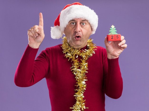 Мужчина средних лет в рождественской шляпе санта-клауса с мишурой на шее держит игрушечные кубики с датой двадцать пять, смотрит в камеру в лабиринте и удивлен, показывая указательный палец, стоящий на фиолетовом фоне