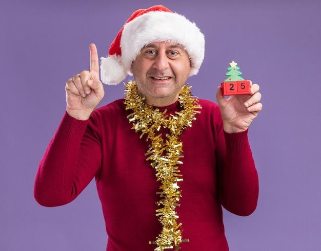 Мужчина среднего возраста в рождественской шляпе санта-клауса с мишурой на шее держит игрушечные кубики с датой двадцать пять, глядя в камеру, улыбаясь, показывая указательный палец, стоящий на фиолетовом фоне