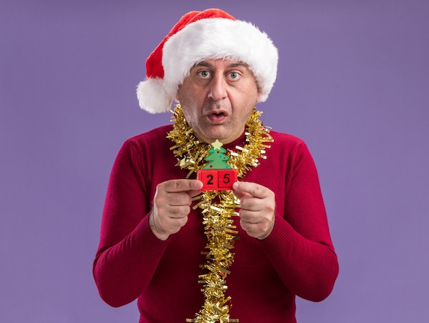 Мужчина средних лет в рождественской шляпе санта-клауса с мишурой на шее держит игрушечные кубики с датой двадцать пять и смотрит в камеру, обеспокоенный и смущенный, стоя на фиолетовом фоне