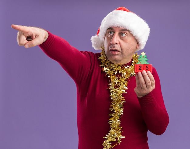 Мужчина среднего возраста в рождественской шапке санта-клауса с мишурой на шее держит игрушечные кубики с датой двадцать пять, указывая указательным пальцем на что-то смущенное, стоя на фиолетовом фоне