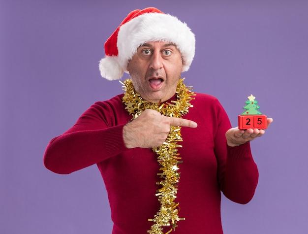 Мужчина средних лет в рождественской шляпе санта-клауса с мишурой на шее держит игрушечные кубики с датой двадцать пять, указывая на них указательным пальцем и удивленно смотрит на них, стоя на фиолетовом фоне