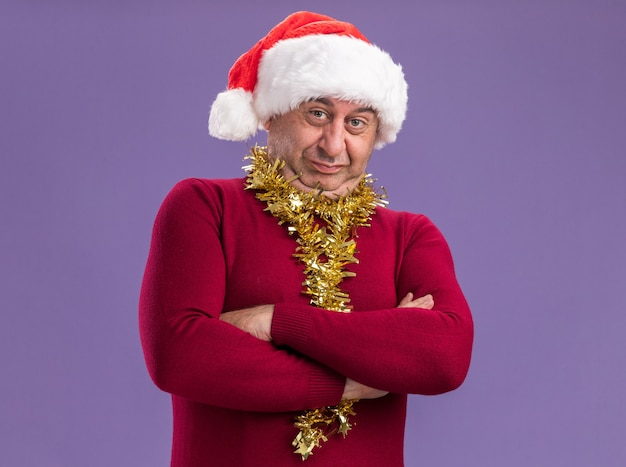紫色の背景の上に立って腕を組んで懐疑的な表情でカメラを見て首の周りに見掛け倒しのクリスマスサンタ帽子をかぶっている中年男性
