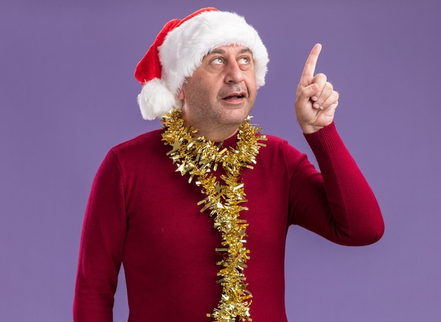 Middle age man wearing christmas santa hat  with tinsel around neck  looking up with smile on smart face showing index finger having new idea  standing over purple background