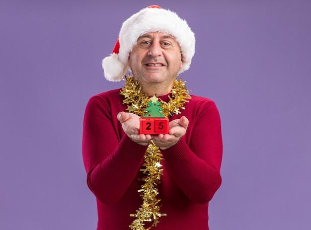 Мужчина среднего возраста в рождественской шляпе санта-клауса с мишурой на шее, показывая игрушечные кубики с датой двадцать пять, глядя в камеру, весело улыбаясь, стоя на фиолетовом фоне