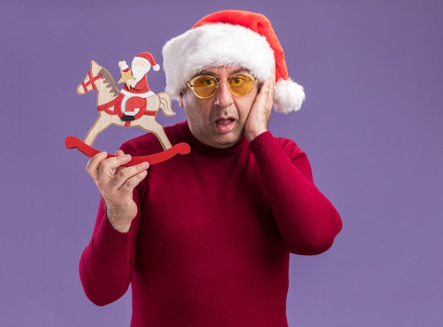 Middle age man wearing christmas santa hat  in yellow glasses showing christmas toy   confused standing over purple wall