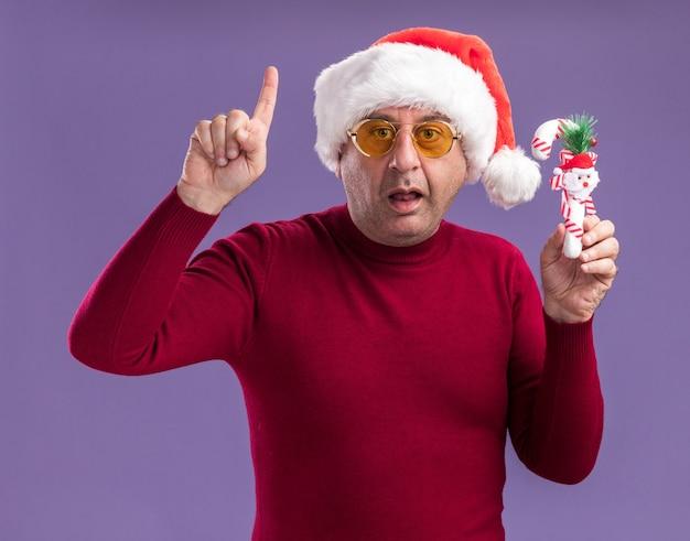 Мужчина среднего возраста в рождественском санта-клаусе в желтых очках, держащий рождественскую конфету, смотрит в камеру с удивлением, показывая указательный палец, стоящий на фиолетовом фоне