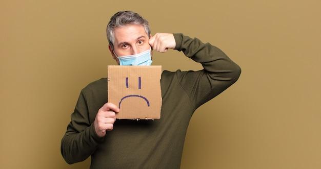 Мужчина среднего возраста с защитной маской и грустной концепцией