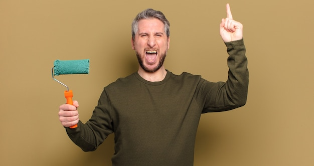 Мужчина среднего возраста с концепцией украшения краски ролика