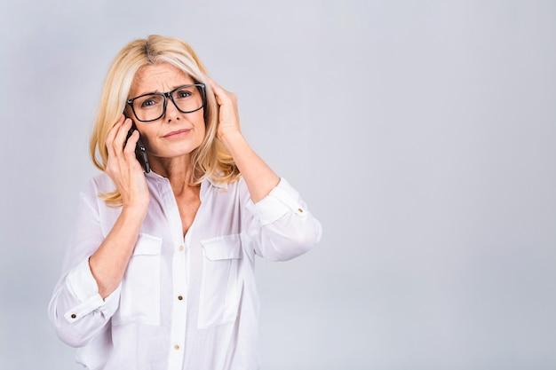 흰색 회색 배경에 격리된 스마트폰으로 이야기하는 중년의 중년 여성은 머리에 손을 대고 스트레스를 받고 수치심과 놀란 얼굴에 충격을 받고 화나고 좌절합니다.