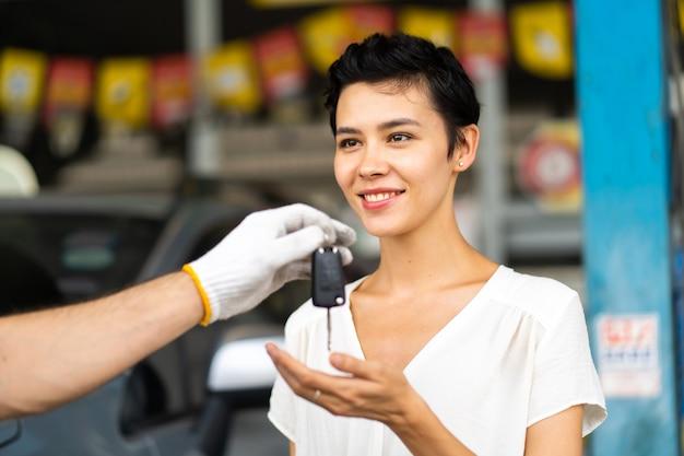 髭を生やした中年の整備士が、車の整備ステーションや自動車サービスガレージで女性客に車の鍵を渡す