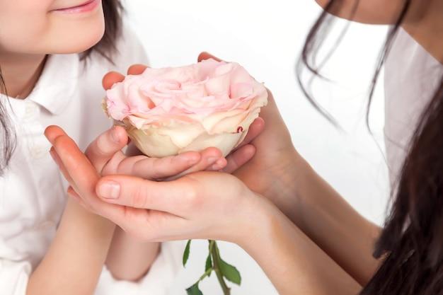 Мать среднего возраста и молодая дочь в белой одежде держат цветок в руках на белом изолированном фоне. женщина обнимает руку ребенка, держащую цветы как символ материнской любви и женского дня. копировать пространство