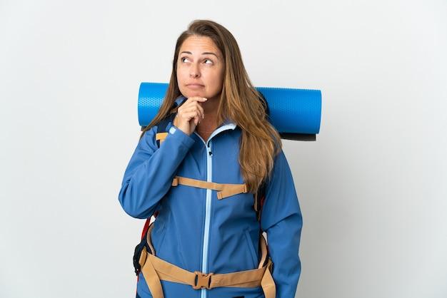 Женщина-альпинист среднего возраста с большим рюкзаком над изолированной и смотрит вверх