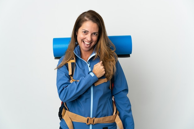 Middle age mountaineer woman with a big backpack over isolated wall celebrating a victory