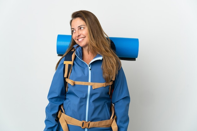 Middle age mountaineer woman with a big backpack isolated